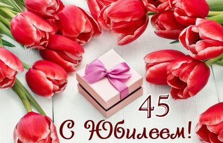 Яркая, красивая открытка с днём рождения на юбилей 45 лет с текстом, с пожеланием и стихом! С юбилеем, с днём рождения, сорок пять лет! Подарок в окружении красных тюльпанов. Скачать открытку на юбилей 45 лет бесплатно онлайн! скачать открытку бесплатно | 123ot
